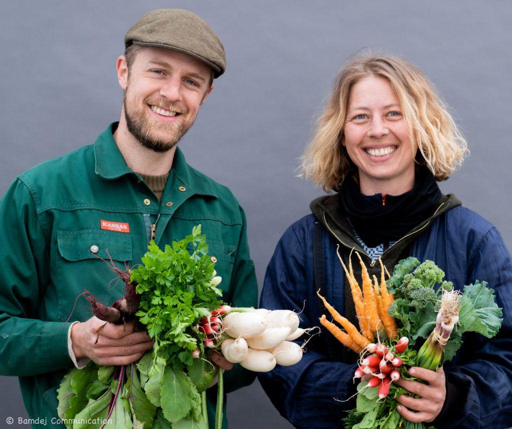 Fredrik og Christina fra Godis Grønt står med favnen fuld af økologiske grøntsager fra egen produktion